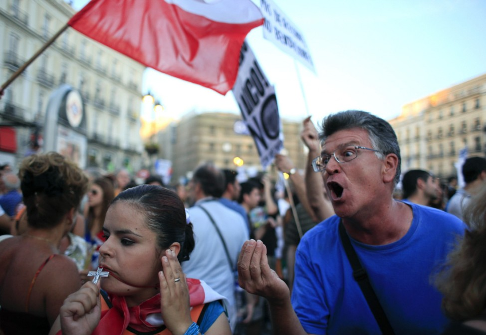 A protester rebukes pilgrims during a demostration against what they claim to be the expensive cost of the papal visit in central Madrid coinciding with the second day of the World Youth Day meeting