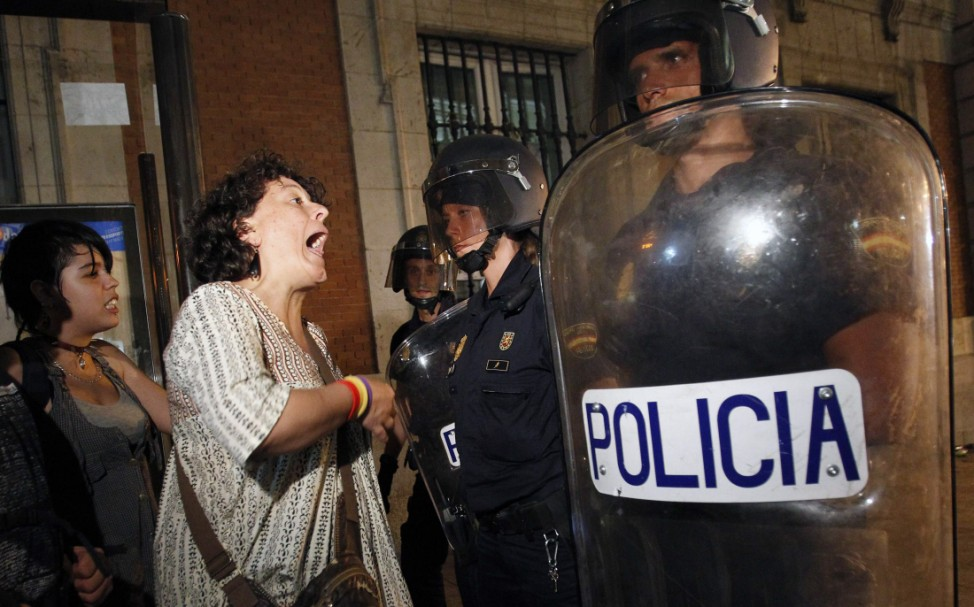 A woman shouts at the police in central Madrid, during a demonstration against the cost of an upcoming visit by Pope Benedict to Spain