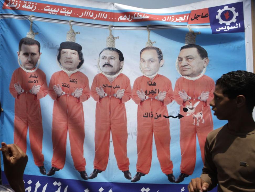 Man looks at banner depicting regional arab leaders in prison garb in Tahrir Square