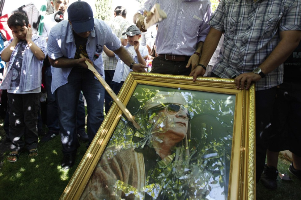 Demonstrators smash a poster of Libyan leader Muammar Gaddafi during a protest against Gaddafi outside of the Libyan embassy in Ankara