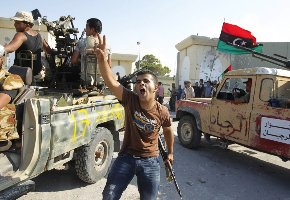 Libyan rebel fighters celebrate after their entering the Bab al Aziziya compound in Tripoli