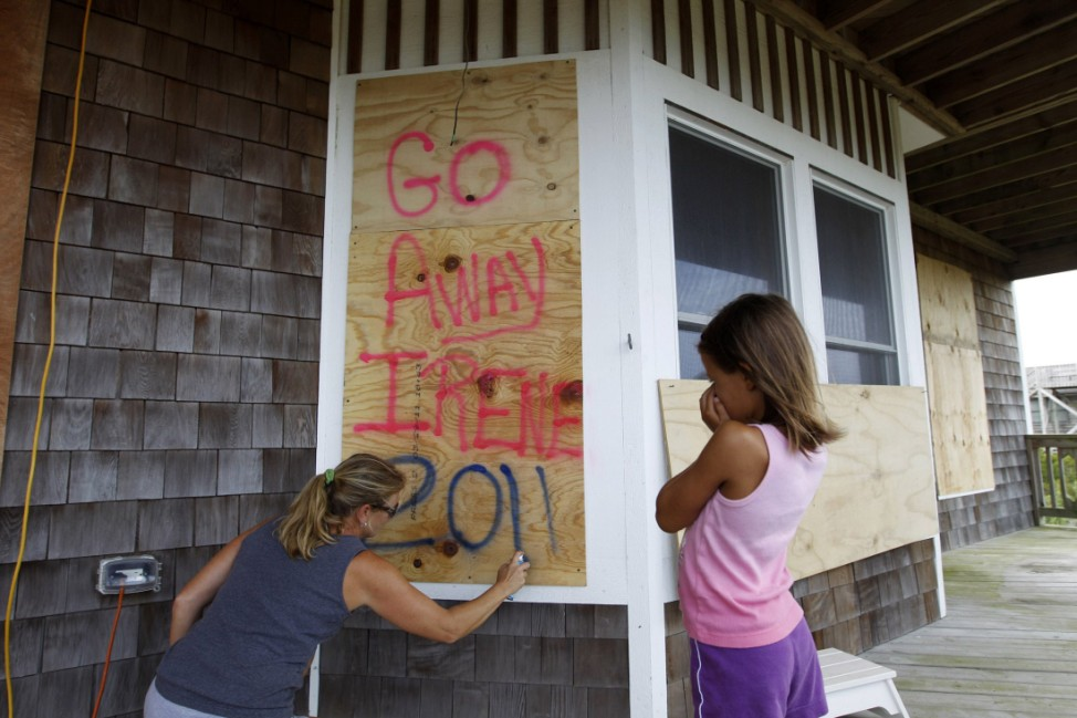 Karlie Philips writes on the boards of her boarded home as her daughter Kylie looks on, at Cape Hatteras National Seashore in Salvo