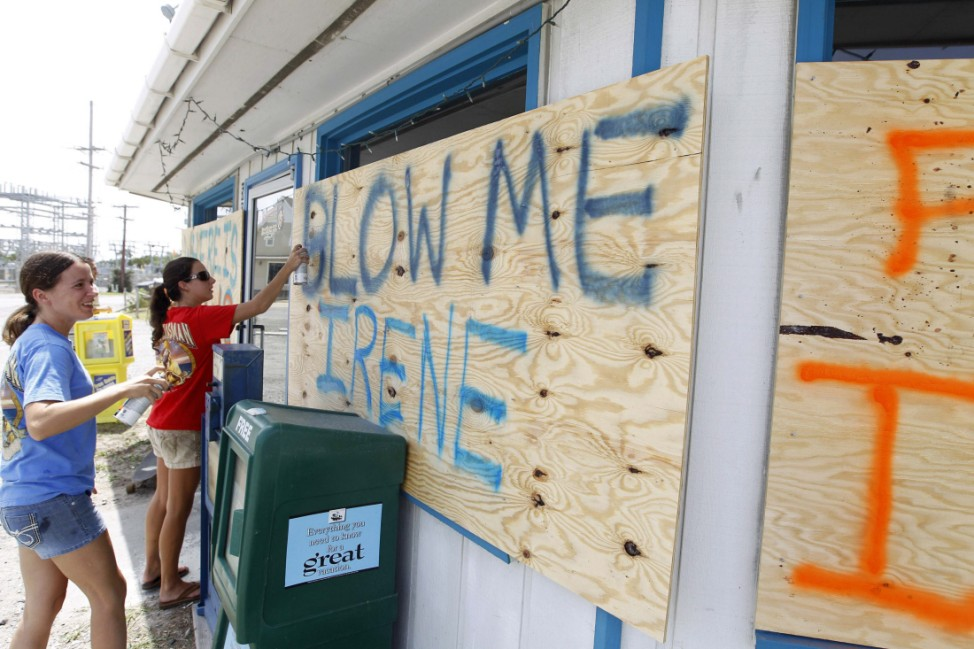 Shop workers Heather Smith and Danielle Batchelor write on the shop's boards at Cape Hatteras National Seashore in Frisco