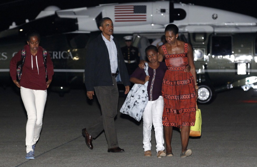 U.S. President Obama and his family walk to board Air Force One after cutting short by a day their vacation on Martha's Vineyard in Massachusetts