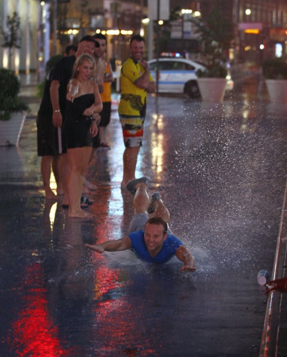 Friends watch as a man slides in the puddles from the rain of Hurricane Irene in New York's Times Square