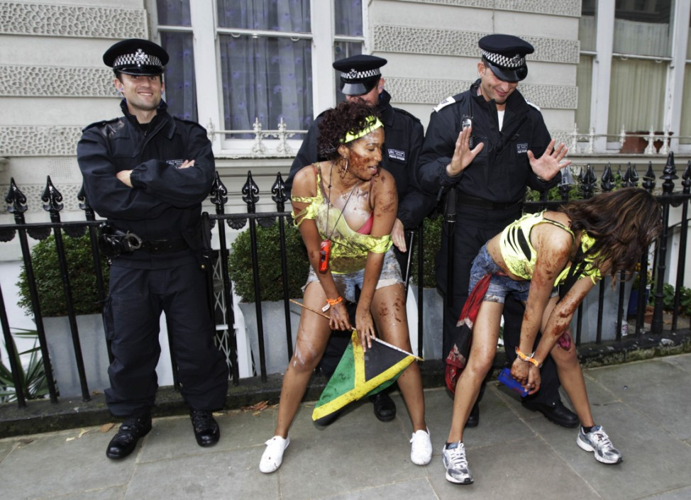 Performers dance in front of police offers during the annual Notting Hill Carnival in central London