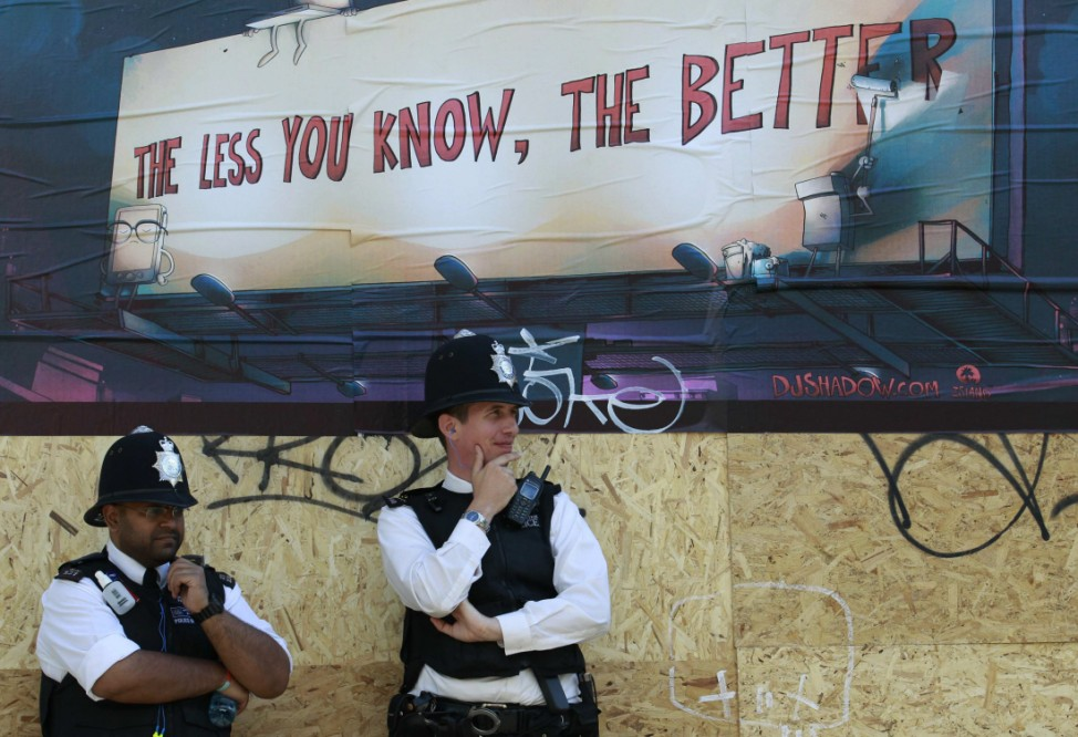 Police stand under a poster during the annual Notting Hill Carnival in central London