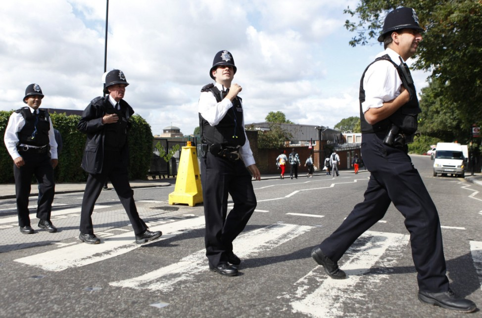 Police officers cross a road during the annual Notting Hill Carnival in London