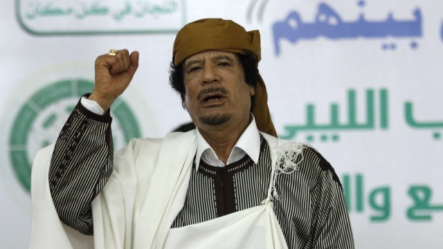 Libyan leader Muammar Gaddafi gestures to his supporters in Tripoli before making a speech