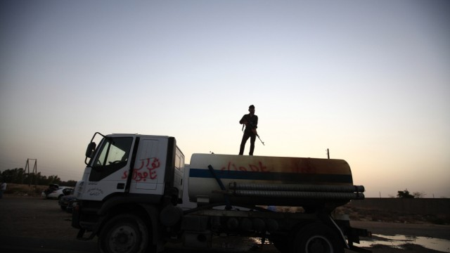 An anti-Gaddafi fighter from the Warfallah tribe stands guard on top of a tanker outside the town of Bani Walid