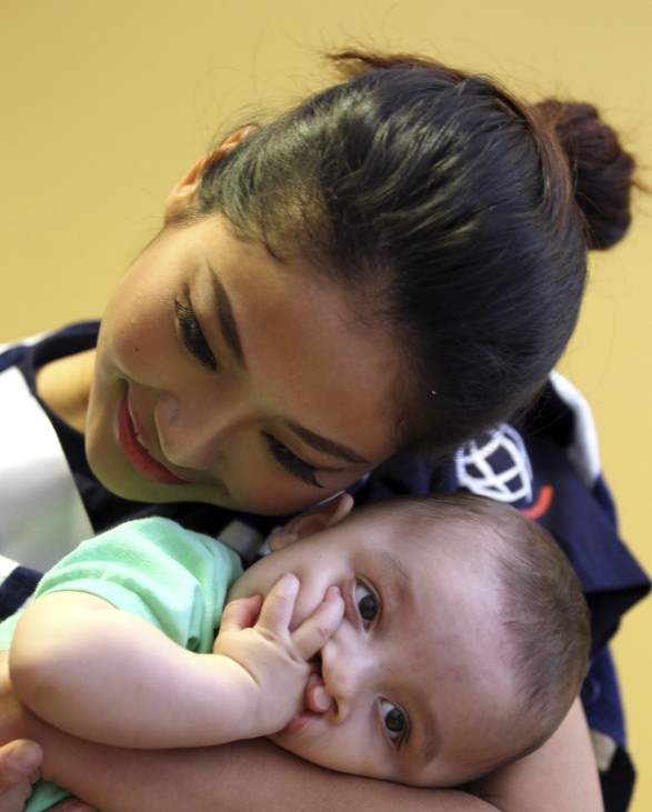 Luo Zilin carries a child with a cleft lip at a hospital during the 'Operation Smile' event in Sao Paulo
