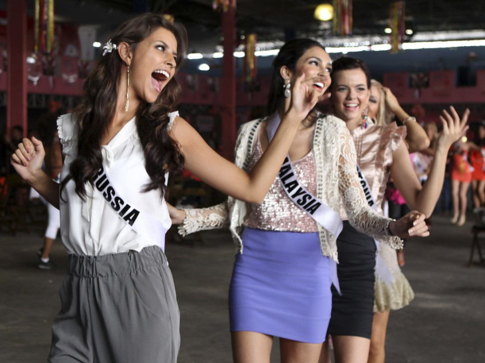 Miss Russia Natalia Gantimurova, Miss Malaysia Deborah Henry and Miss Estonia Madli Vilsar attend a samba dance class at Rosas de Ouro samba school in Sao Paulo