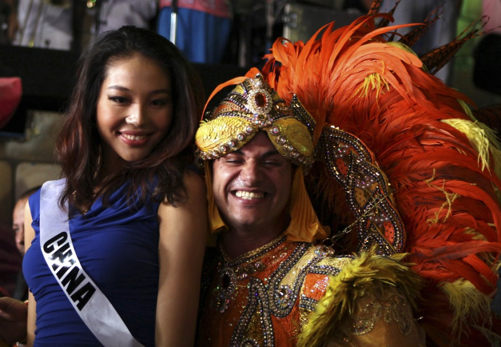 Miss China 2011 Luo Zilin poses for a photograph with a member of Rosas de Ouro samba school in Sao Paulo