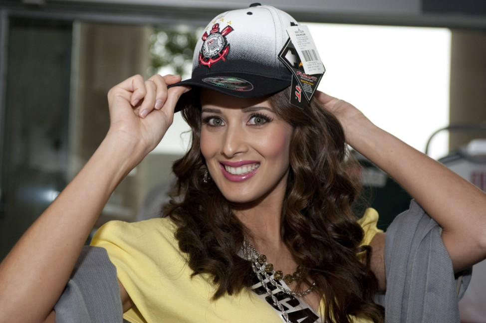 Miss Nicaragua Adriana Dom tries on a cap at the Soccer Museum in Sao Paulo
