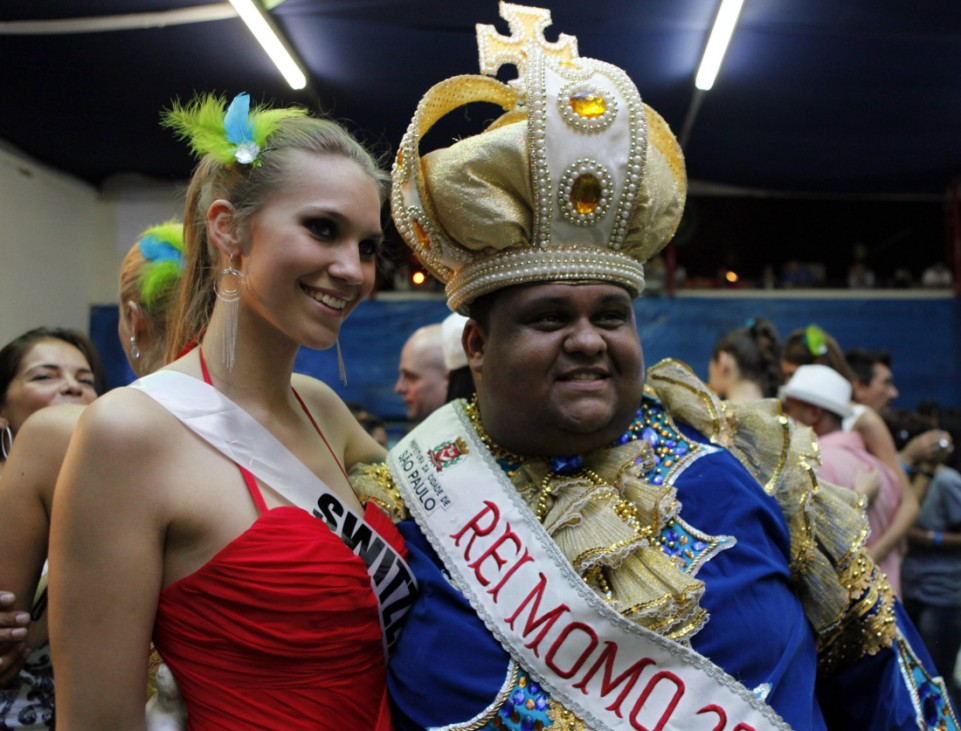 Miss Switzerland 2011 Cook poses for a photograph with a member of the Vila Maria samba school in Sao Paulo