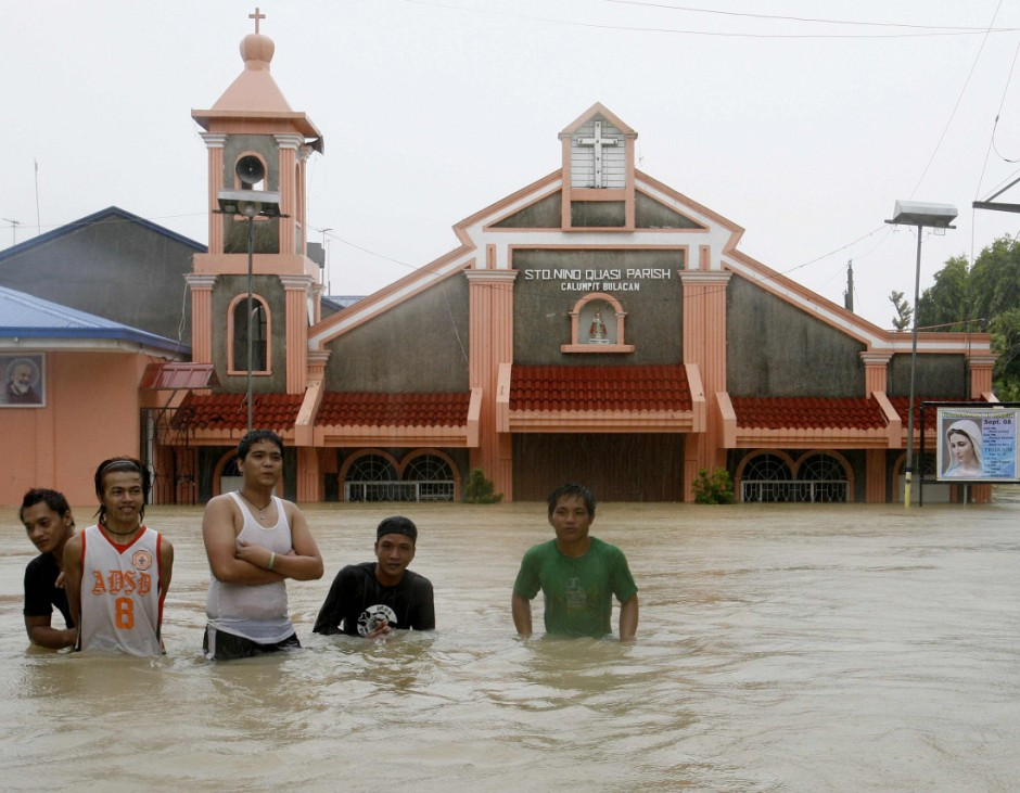Residents wade through floodwaters after typhoons submerged a church, homes and other establishments in Calumpit