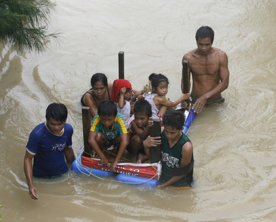 A family uses a table as a makeshift raft to evacuate their children to higher grounds after massive flooding brought on by typhoons in Calumpit