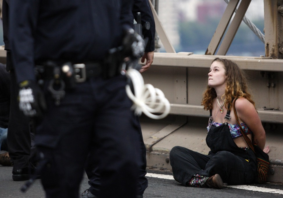A protester looks up at a police officer after being arrested on the Brooklyn Bridge during an Occupy Wall Street protest in New York