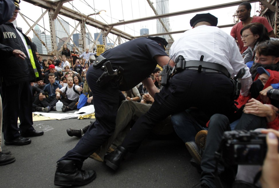 Police officers reach into a crowd of protesters to make an arrest on the Brooklyn Bridge during an Occupy Wall Street march in New York
