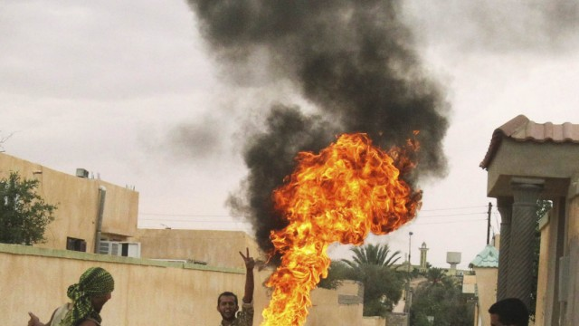 Anti-Gaddafi fighters burn a flag of the Gaddafi regime that they found during a house search after taking control of the town of Bou Hadi in Sirte