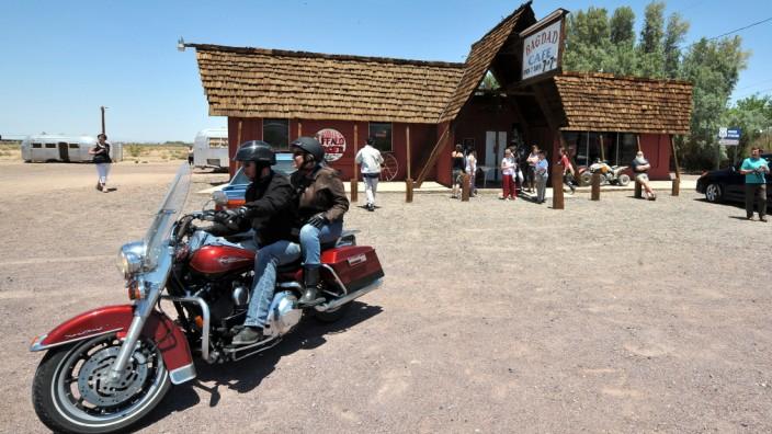 """Unterwegs auf der Route 66: Eine Harley-Davidson vor dem Bagdad Cafe in Newberry Springs, Kalifornien, an der alten U.S. Route 66 - jetzt nur noch San Bernardino County Route 66. Das frühere Sidewinder Cafe wurde nach den Dreharbeiten für den Film """"Out of Rosenheim"""" umbenannt."""
