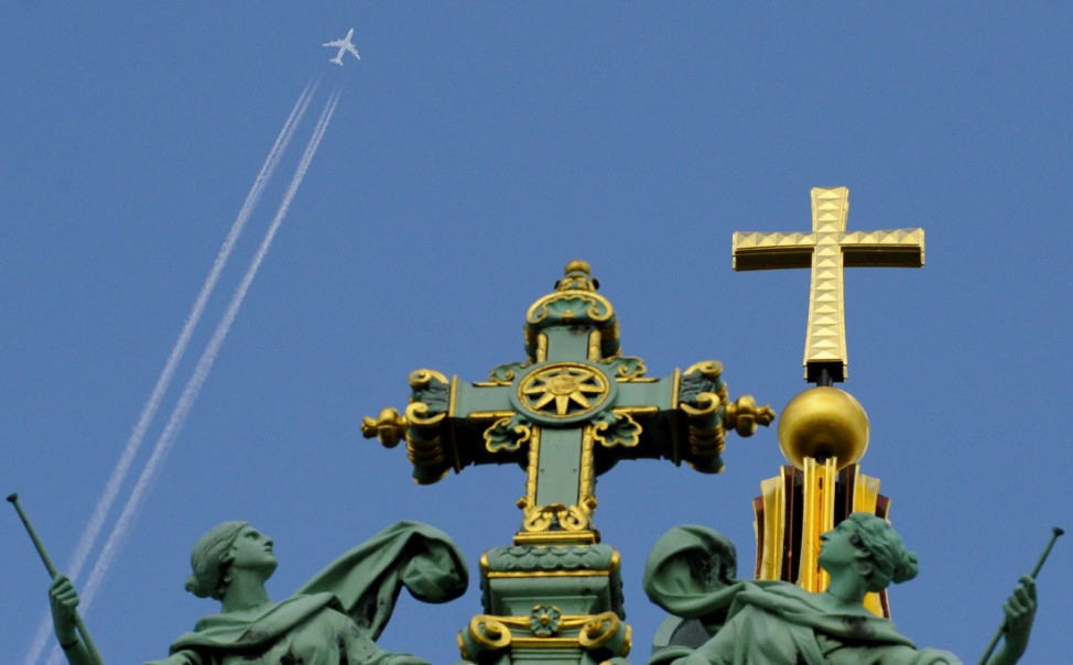 Flugzeug über dem Kreuz des Berliner Doms
