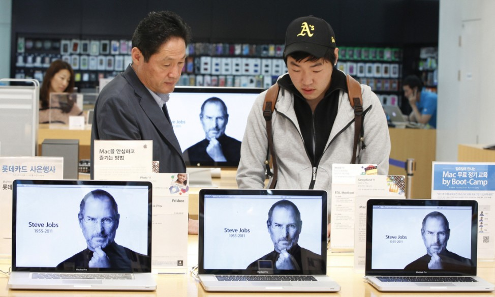 Customers look at products behind computer monitors displaying the obituary of former Apple CEO Steve Jobs at an Apple Store in Seoul