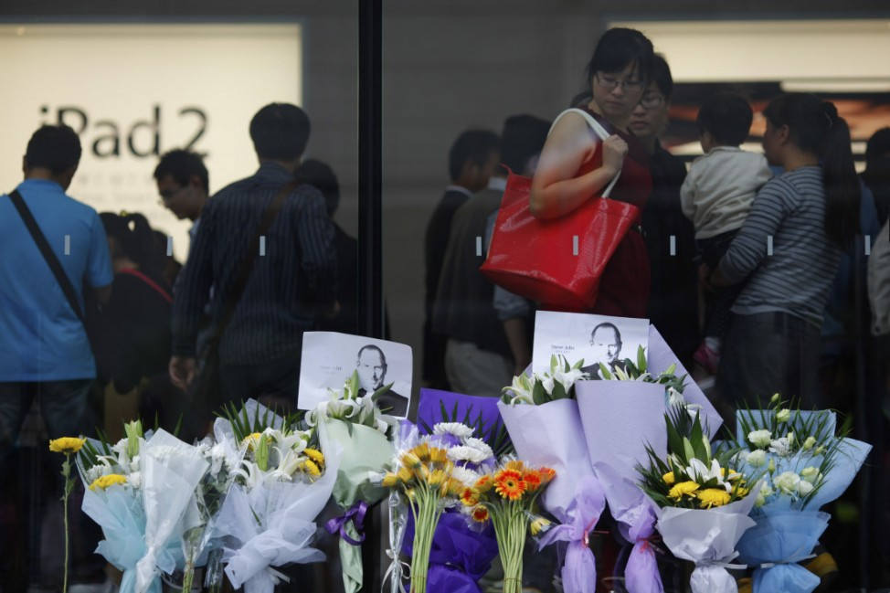 Flowers in memory of Apple co-founder Jobs are placed outside an Apple Store in downtown Shanghai