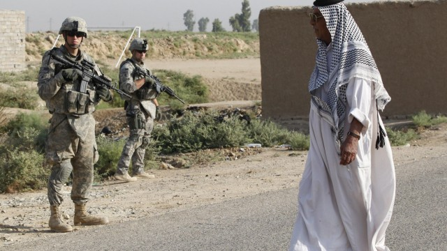 A resident walks past U.S. Army soldiers standing guard during a joint patrol with the Iraqi Army on the outskirts of Kut