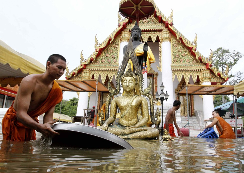 Buddhist monks collect their belongings at a flooded temple in Ayutthaya province