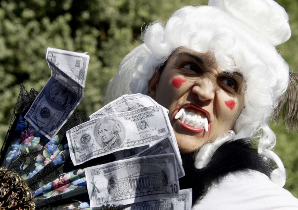 A demonstrator holds copies of U.S. ten dollar banknotes during a demonstration against banking and finance in Rome