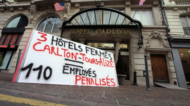 A placard which reads '3 hotels closed, Carlton-Tours-Alize, and 110 jobs penalized' is seen in front of the Hotel Carlton in Lille