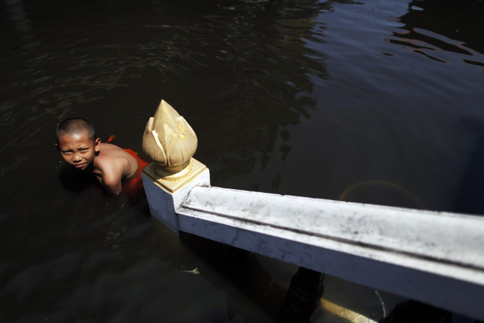 A novice Buddhist monk wades through water at the flooded Wat Preak Prachkor temple in Pathum Thani province