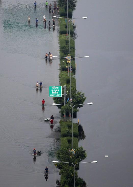 People walk on one side of a flooded highway in the suburbs of Bangkok