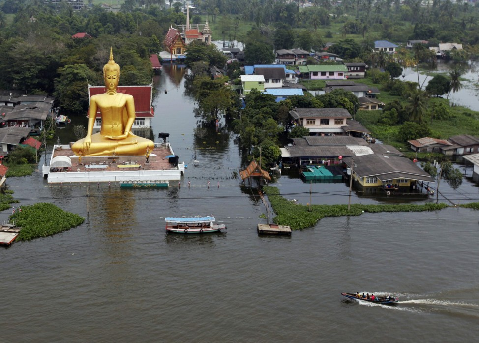 A boat sails past a giant statue of Buddha in a flooded temple just outside Bangkok