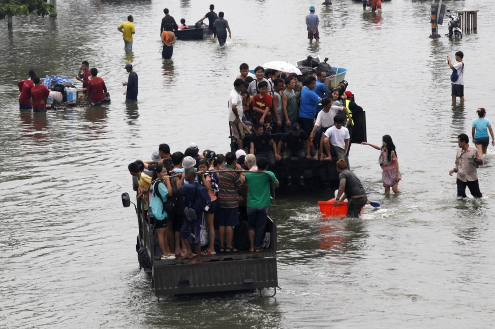 People are evacuated on trucks from a flooded area in Bangkok's suburbs