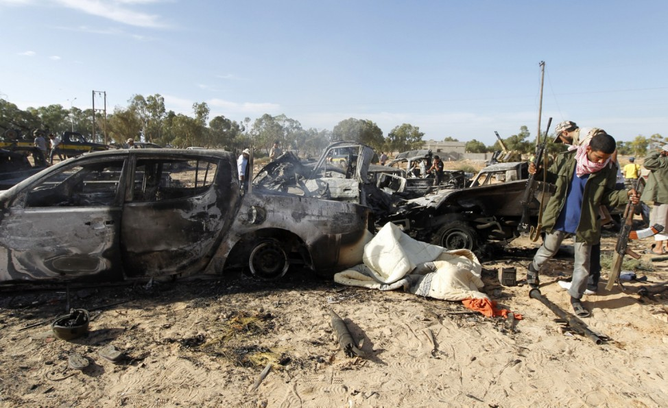 A convoy of Gaddafi loyalists' vehicles is pictured destroyed and littered with bodies near Sirte