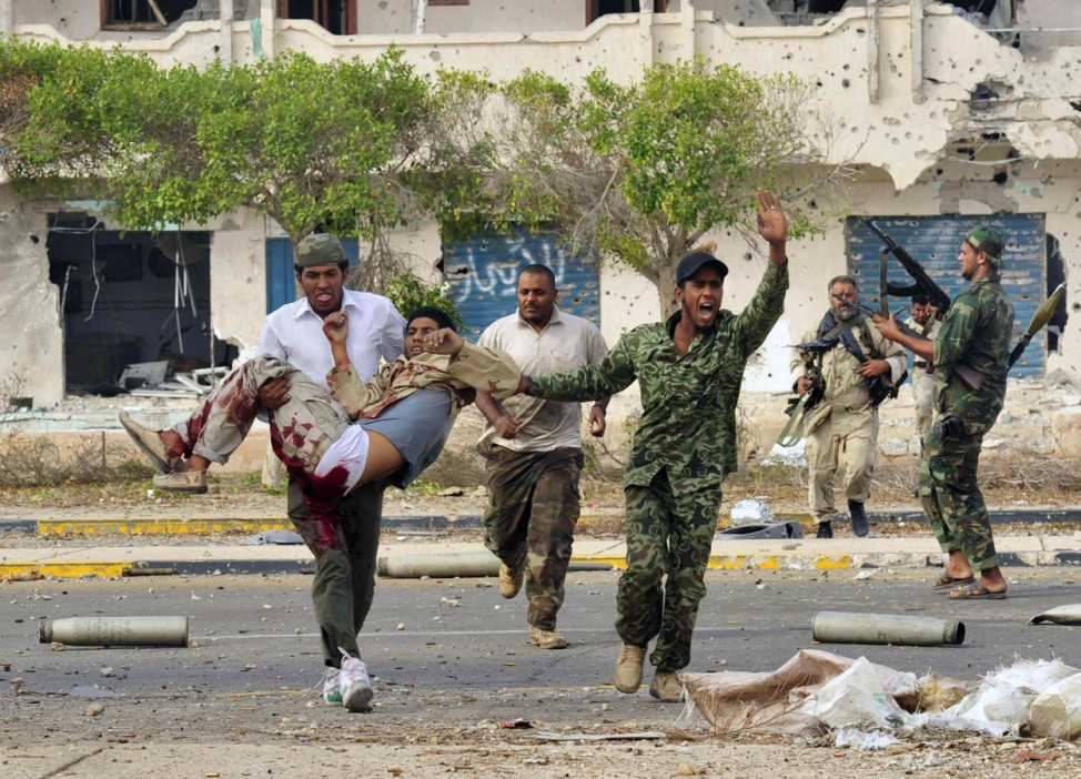 Anti-Gaddafi fighters carry an injured comrade during clashes with Gaddafi forces in Sirte