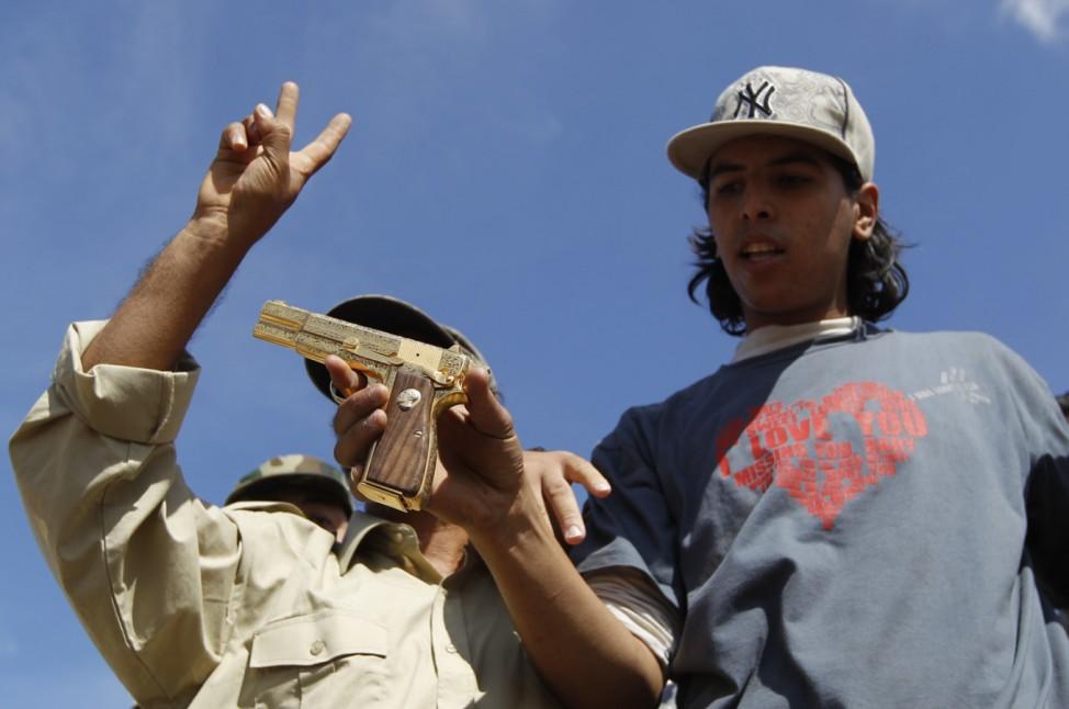 Anti-Gaddafi fighters show the media what they claim was the golden pistol of Muammar Gaddafi, near Sirte