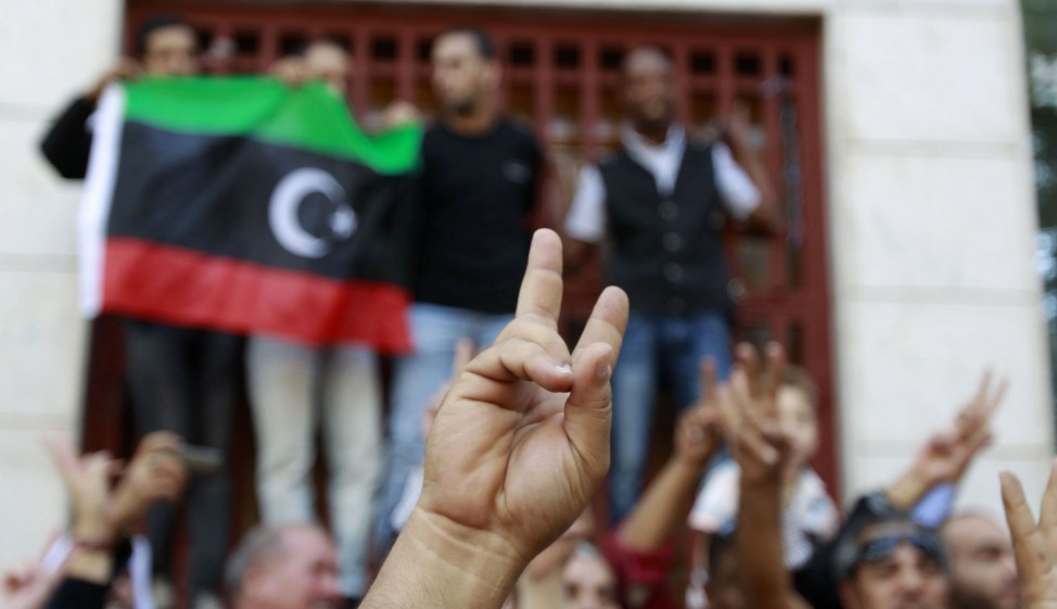 Libyan refugees in Tunisia celebrate after hearing news that Libyan leader Muammar Gaddafi was killed in Sirte, outside their embassy in Tunis October