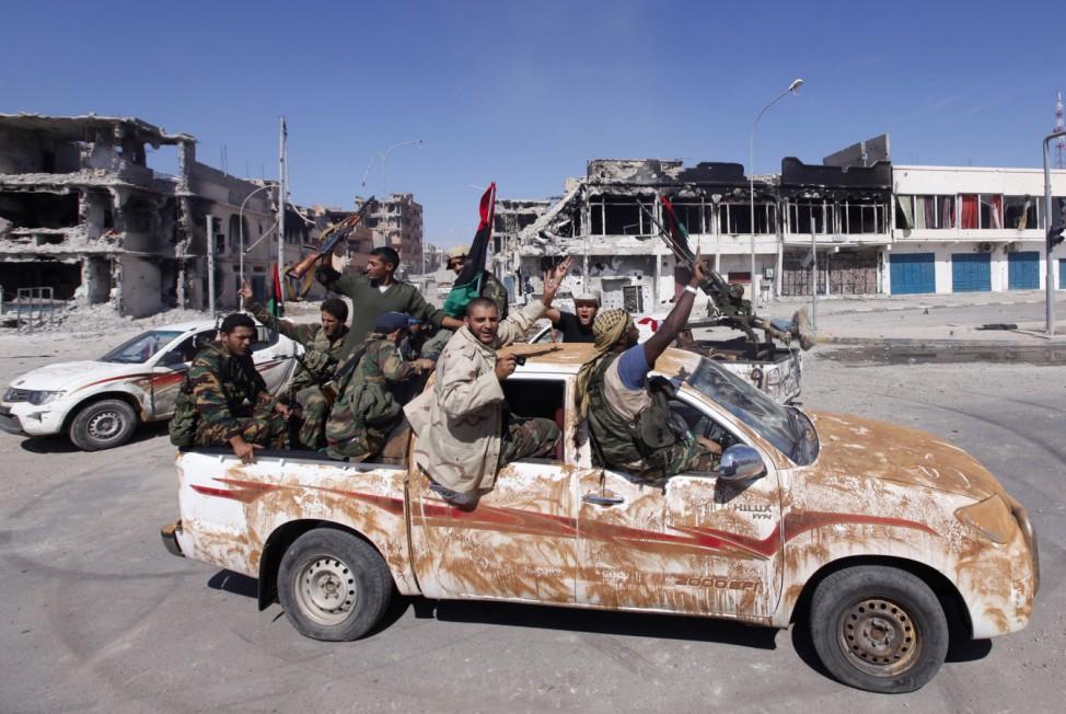 Anti-Gaddafi fighters celebrate the fall of Muammar Gaddafi in Sirte