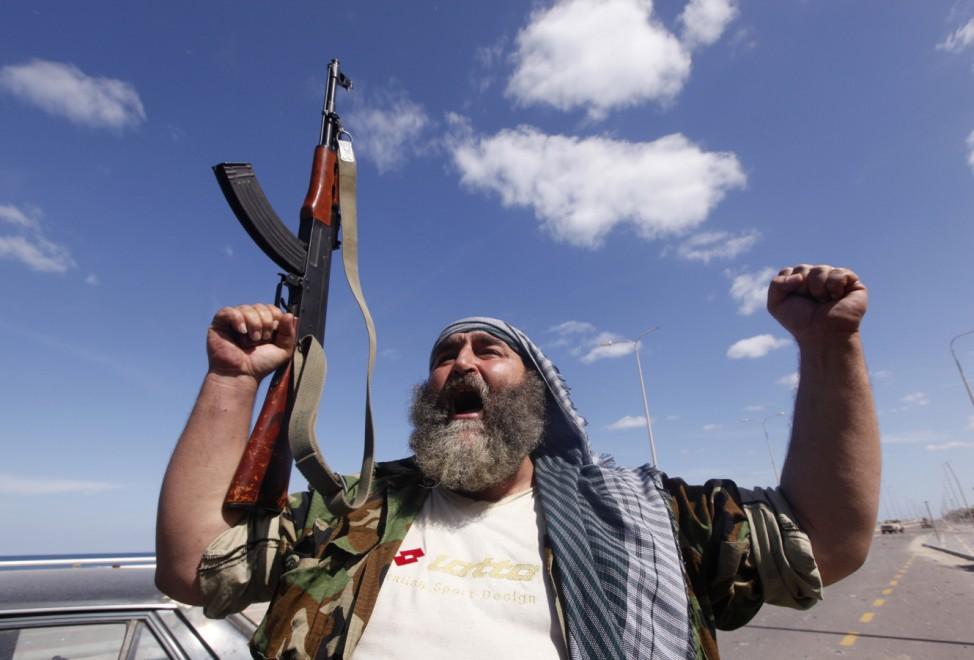 An anti-Gaddafi fighter shouts 'Allahu akbar' (God is great) as he celebrates the fall of Gaddafi in Sirte