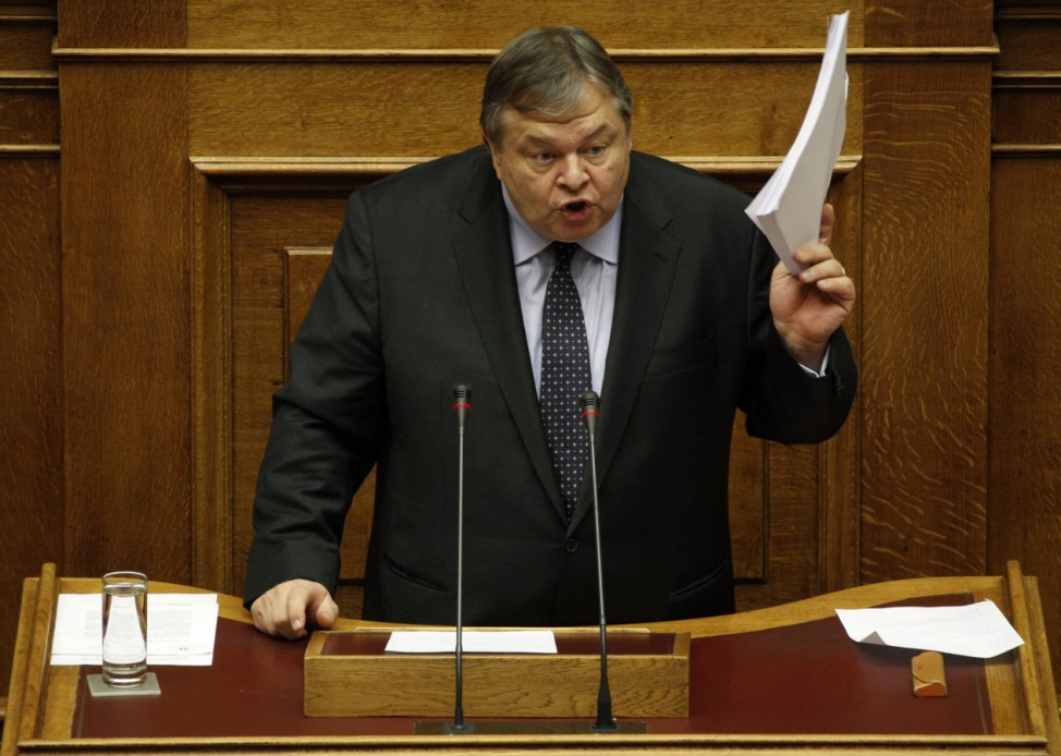 Greece's Finance minister Evangelos Venizelos raises documents as he delivers a speech during a parliament session in Athens