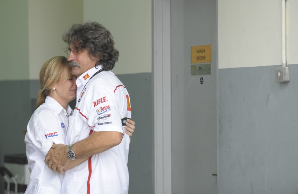 Paolo, the father of Marco Simoncelli of Italy, is consoled inside the pit during the Malaysian Grand Prix in Sepang