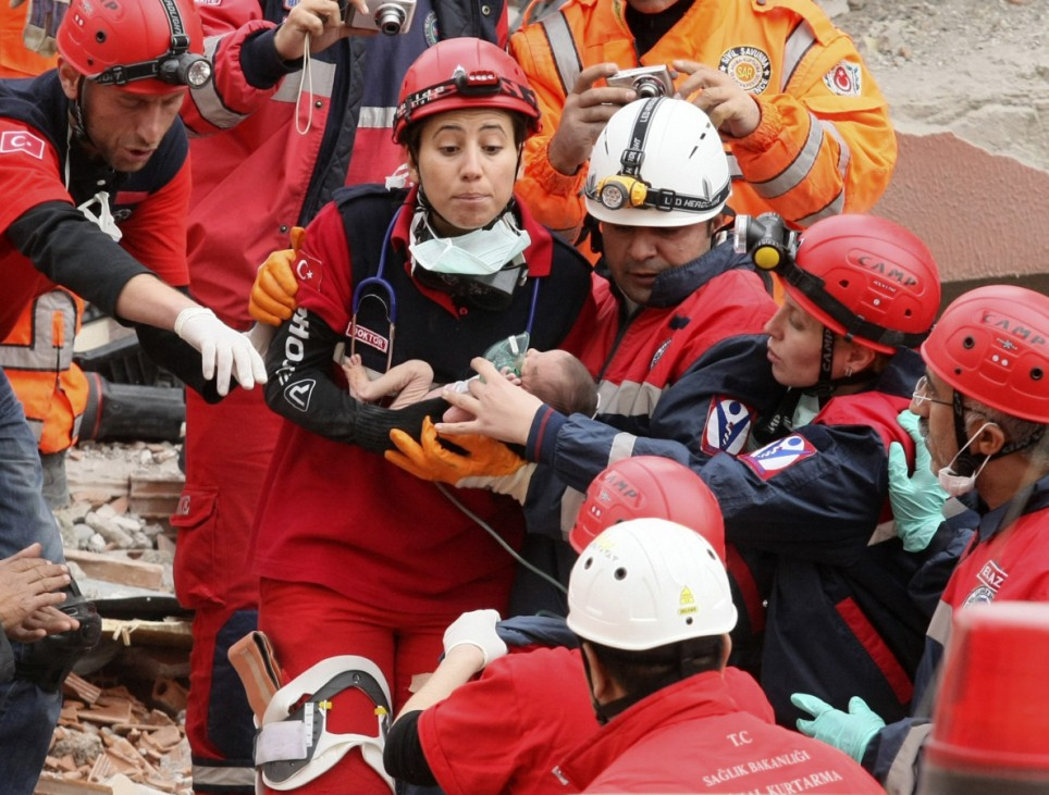 Rescue workers carry a baby from a collapsed building in Ercis