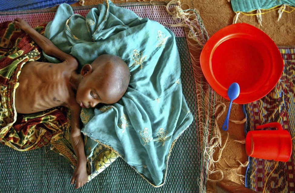A malnourished infant lies on the floor in a therapeutic feeding center in southern Niger.