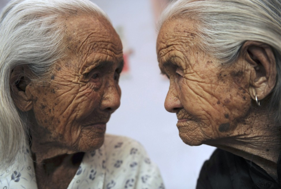 Chinese 104-year-old twins Cao Xiaoqiao and her elder sister Daqiao look at each other in Zhucheng