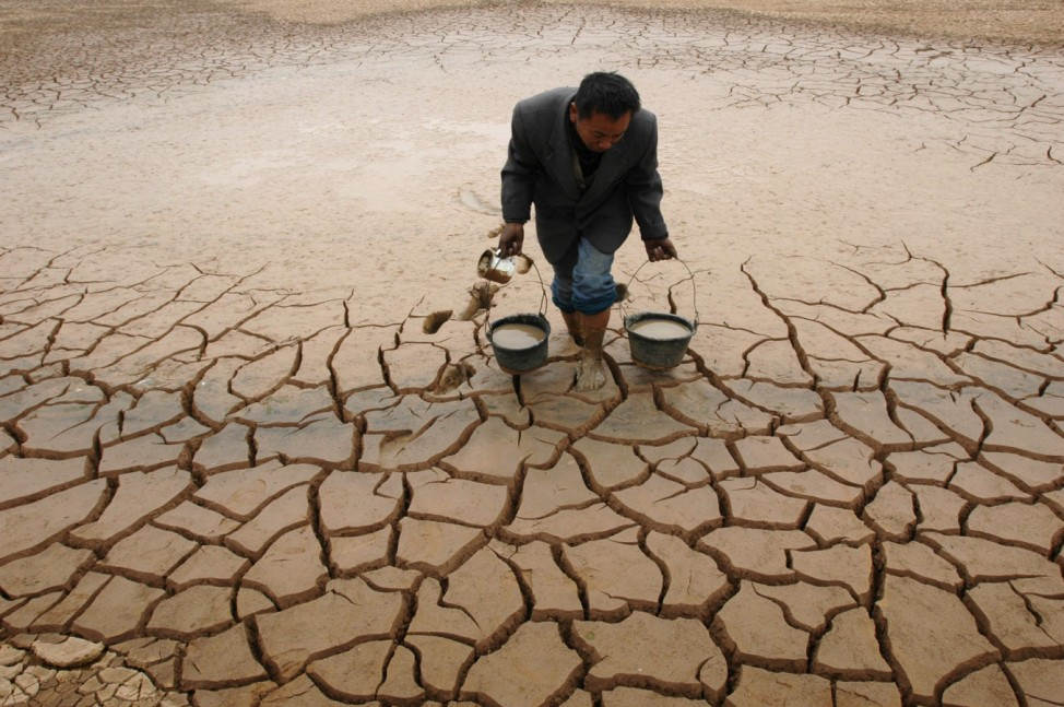 Farmer takes water form a dried-up pond to water his vegetable field on the outskirts of Yingtan