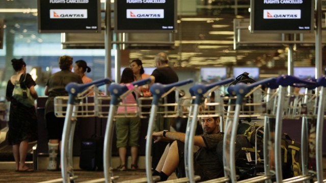 Stranded Qantas passengers wait in front of Qantas check-in counters as they seek alternative travel arrangements at Singapore's Changi Airport