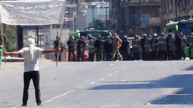 A protester faces riot police at Khalidia